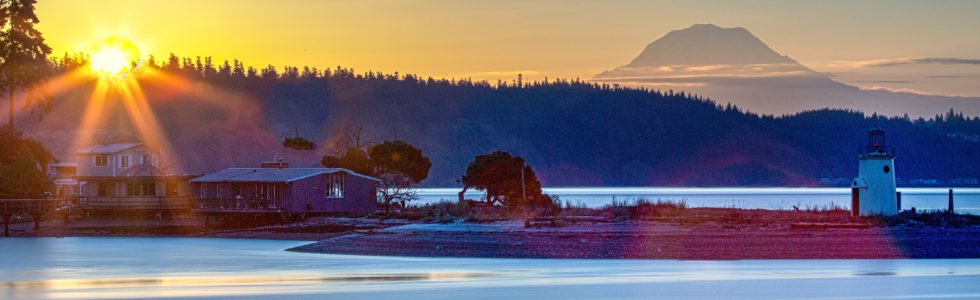 A panoramic photo of Gig Harbor in early Fall with the sunrise and Rainier Mountain the background.