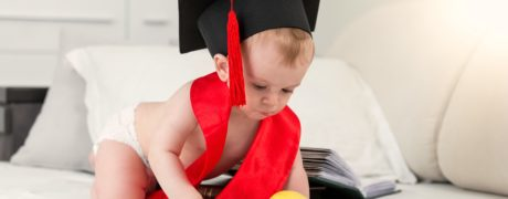 Prodigy baby in graduation cap and red ribbon reaching for apple