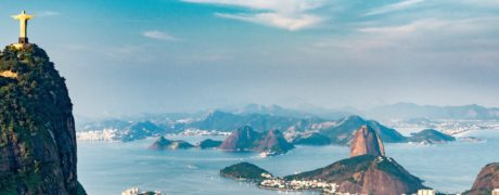 Aerial view of Rio De Janeiro with the statue of Christ the Redeemer overlooking the city in the foreground.