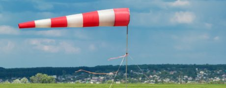 A red, white striped wind vane blowing against a sky background