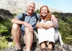 Portrait of a delighted senior couple seated on a mountain top with a smile.