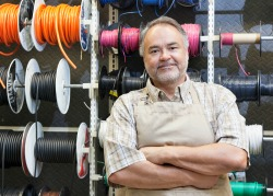 A content, middle-aged small business owner standing in front of electrical wire spool in his hardware store.