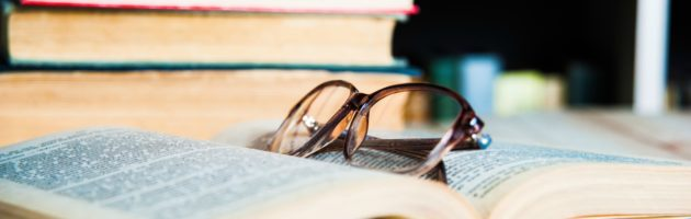 A close up picture of an open book with a pair of glasses laying on top of it.