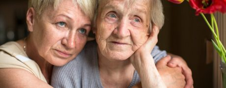 An elderly widow being comforted by her daughter.