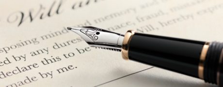 Last will and testament document with closeup on fountain pen with signature line.