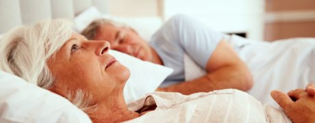 Older woman lying awake in bed worrying about something