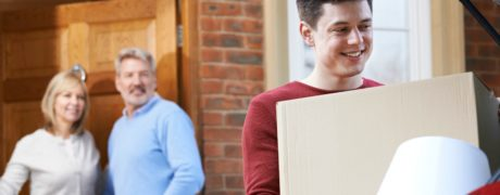 Young adult son loading a box into his car as he moves out of his parents' home