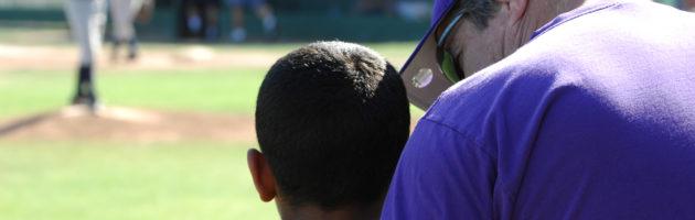 A little league coach consoles a player.