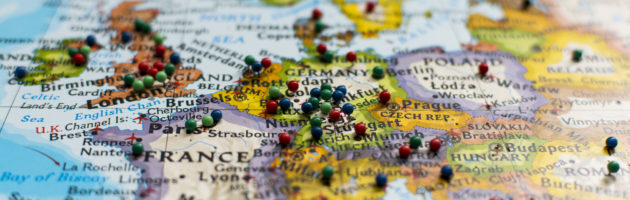 Map of Europe with many colorful thumbtacks on it.