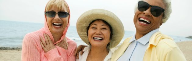 Three older women friends laughing while standing on a beach.