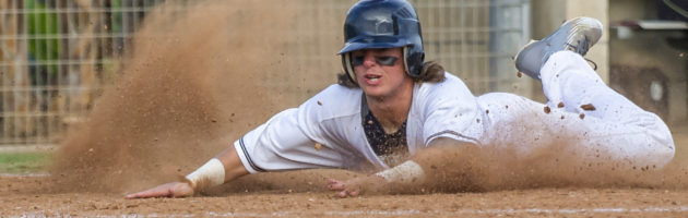 Baseball player slides head first into home base to score a run.