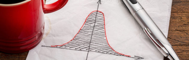 Bell curve on white napkin with a cup of coffee to left