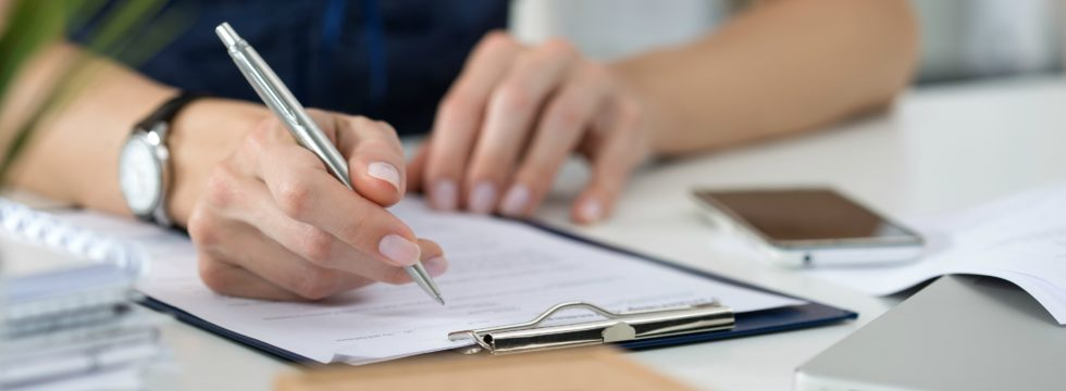 Close-up of female hands filling out form at her work desk.