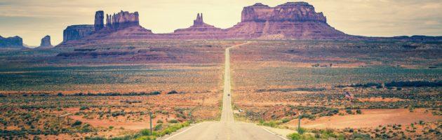 Desert road heading into a distant horizon.