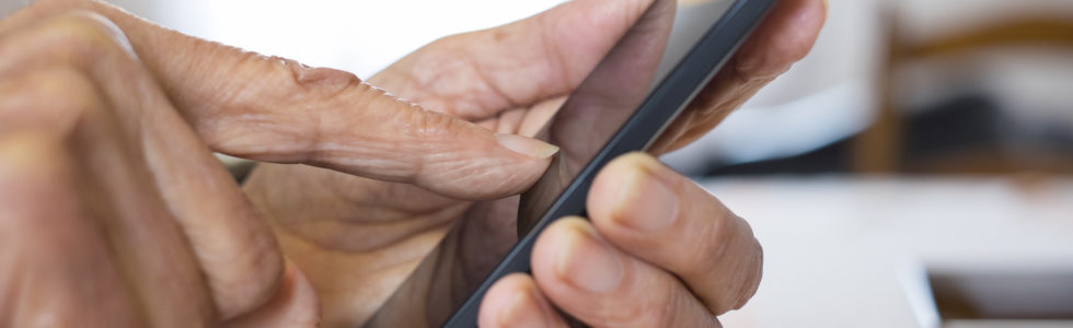 Close up of a senior woman's hands using a smartphone to contact us