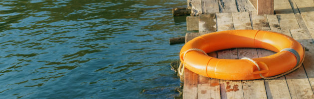 Orange lifebuoy lying unused on a wooden pier to suggest insurance against disaster