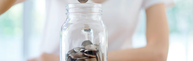 Young woman dropping coins in jar as a form of retirement savings.