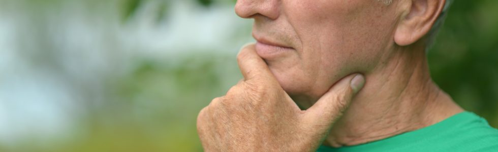 Senior man thinking deeply while standing out-of-doors