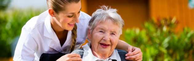 Senior woman in a nursing home with a nurse tending to her