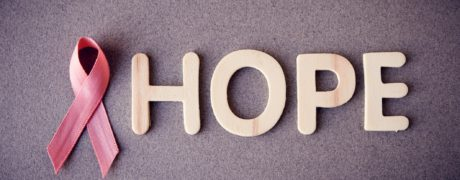 Pink ribbon that symbolize fight against breast cancer next to the word HOPE spelled out in wooden letters.